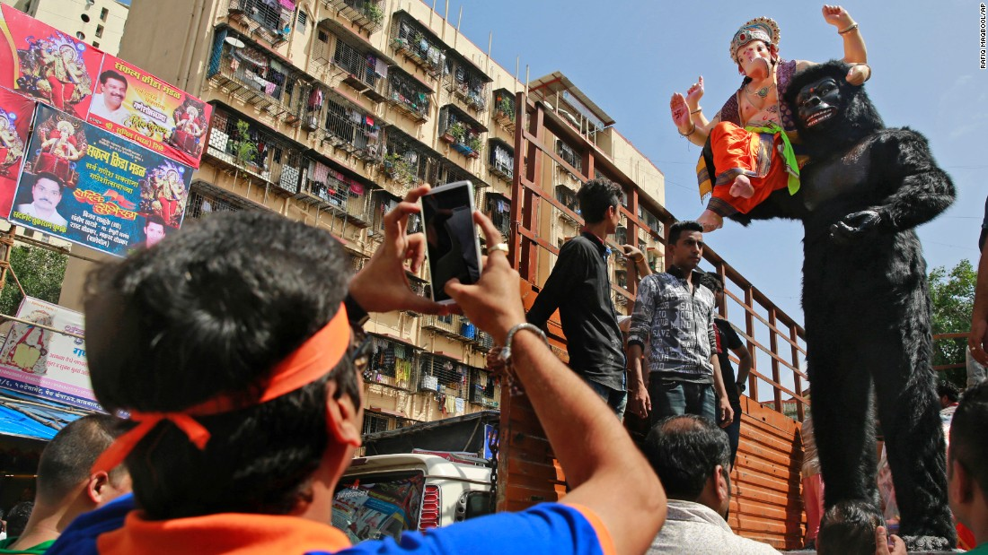 A devotee takes photos of an idol of elephant-headed Hindu God Ganesha with a likeness of a gorilla during celebrations in Mumbai, India, on September 5.