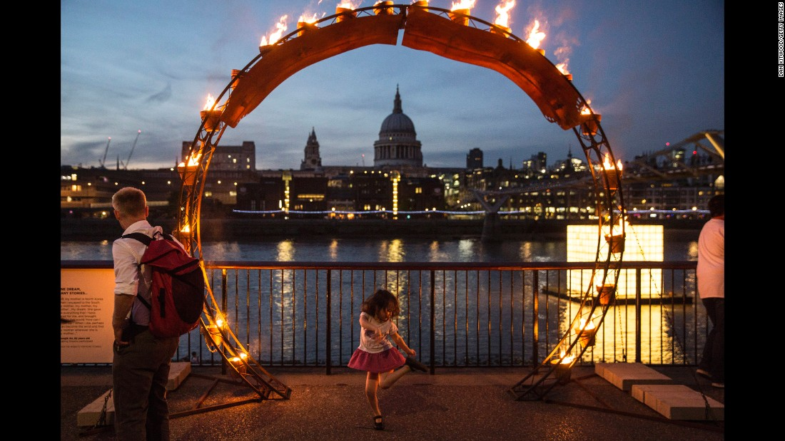 A young girl dances beneath the installation in front of St Paul's Cathedral.