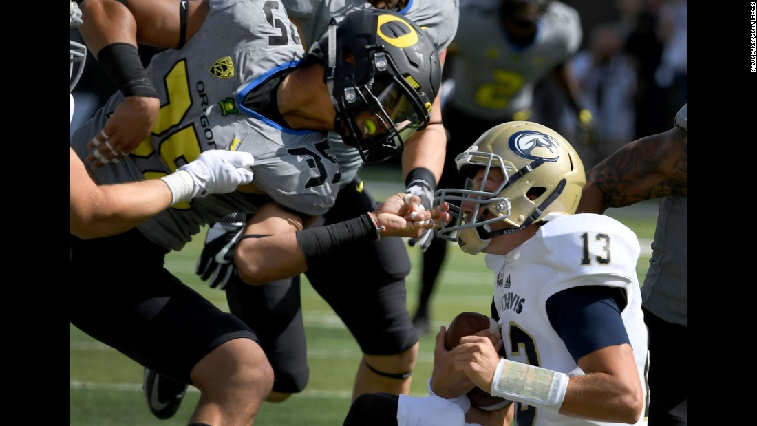 Oregon's Troy Dye, left, grabs the helmet of UC Davis' Ben Scott during a game in Eugene, Oregon, on Saturday, September 3. Oregon defeated UC Davis 53-28.