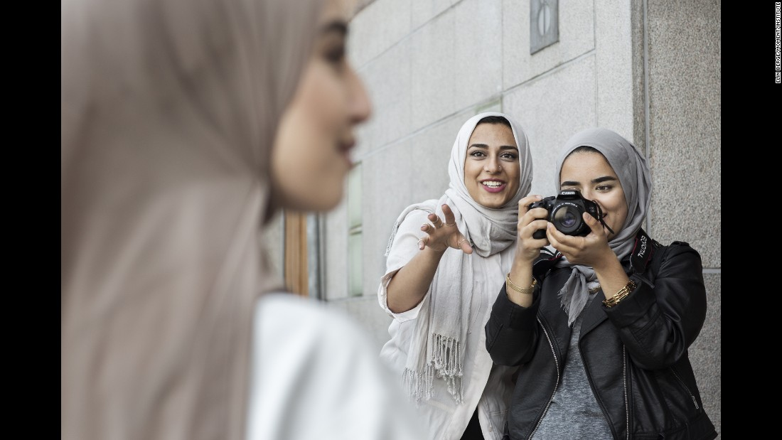 Friends and fashion enthusiasts Imane Asry, Shama Vafaipour and Maryam Dinar take photographs.