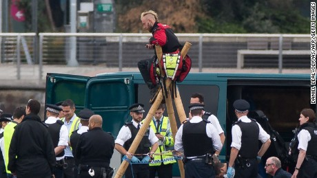 "Emergency services surround protestors from the movement Black Lives Matter after they locked themselves to a tripod on the runway at London City Airport in London on September 6, 2016. Flights at London City Airport have been delayed after Black Lives Matter protesters crossed the dock and ""occupied"" the runway. / AFP / DANIEL LEAL-OLIVAS        (Photo credit should read DANIEL LEAL-OLIVAS/AFP/Getty Images)"