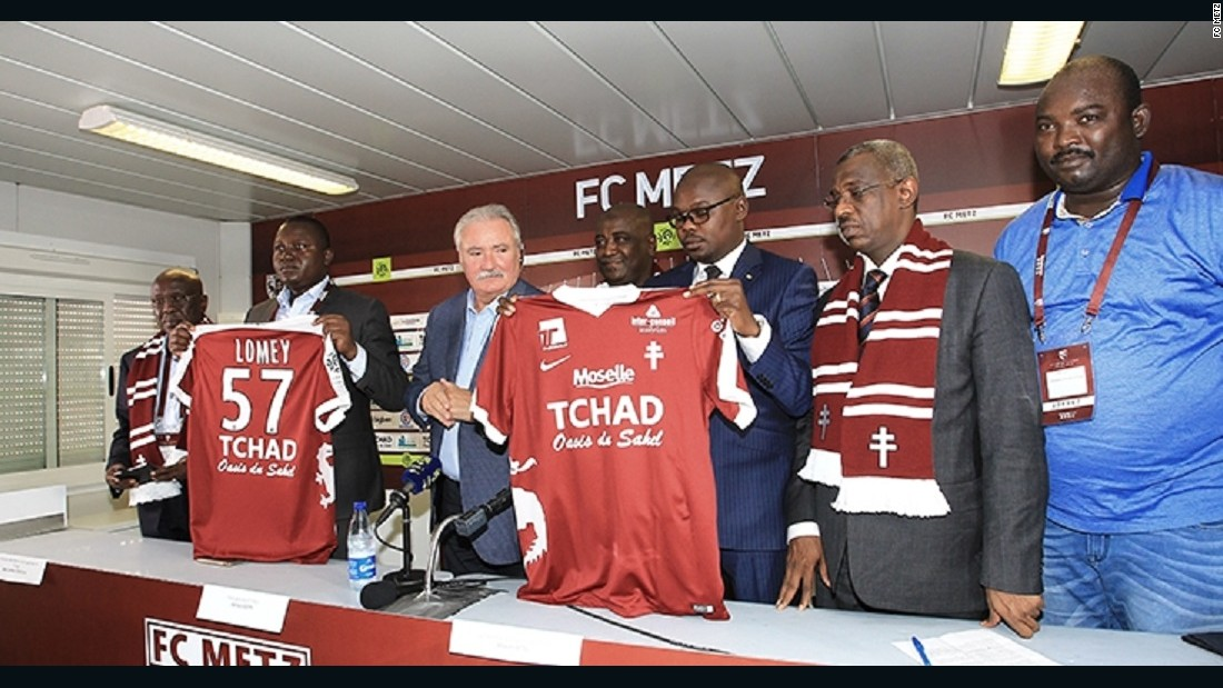 "FC Metz President Bernard Serin appears with Chad Minister of Culture, Youth and Sport Betel Miarom to announce the sponsorship agreement, which will see the French club play with ""Chad: Oasis of the Sahel"" on the team shirts. <br /><br />Chadian officials believe the deal will improve their public image and encourage tourism to the Central African state."