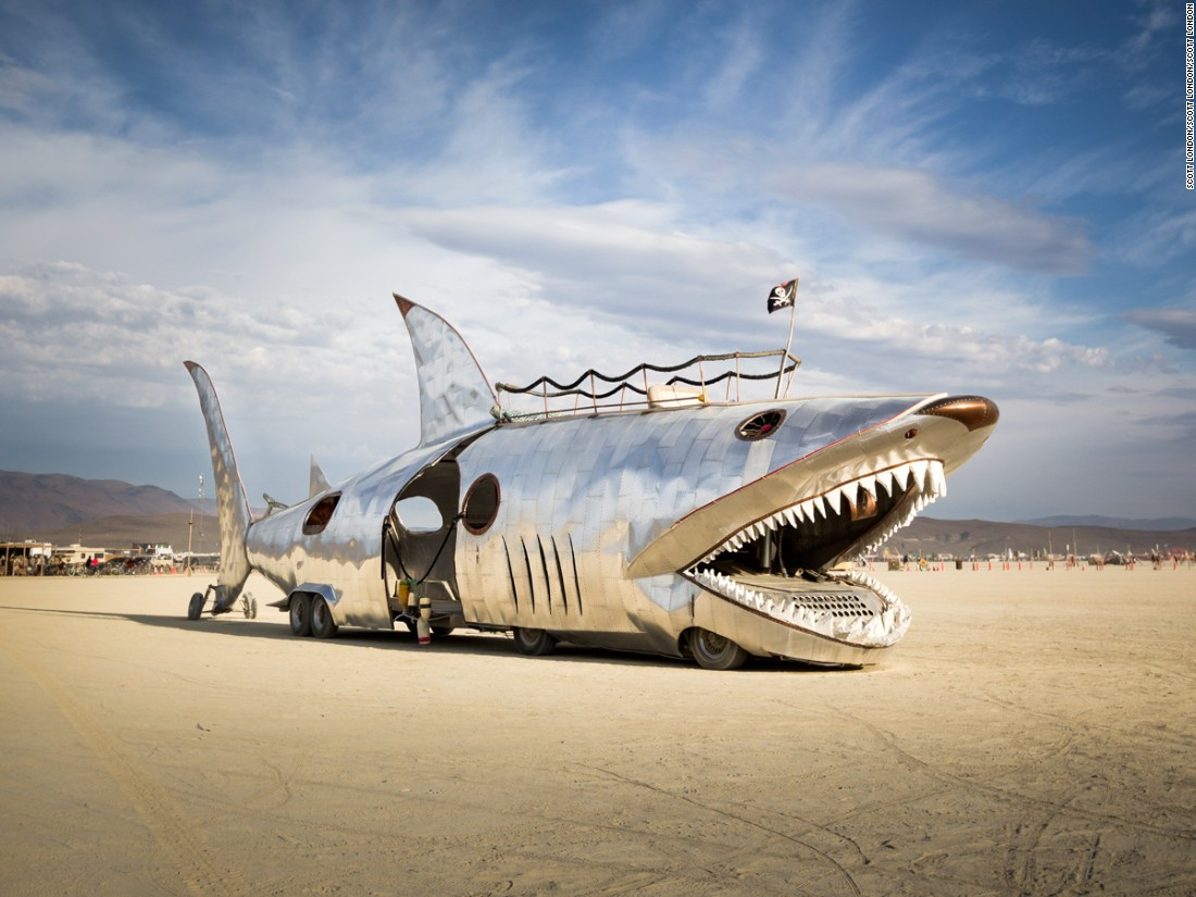 """This art car has a long history at Burning Man, first appearing in 2002. Originally created by Sid Kurz, it belongs to the Seattle-based Lodi Camp. The Shark Car has undergone many redesigns over the years. It returned with a shiny aluminum finish in 2016 but spent much of the week out of commission."""