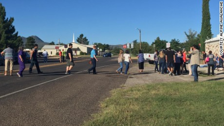 People cross a street as Alpine High School is evacuated following a shooting there Thursday morning.