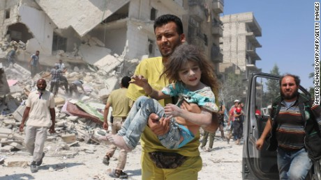 A Syrian man carries a wounded child in eastern Aleppo in August.