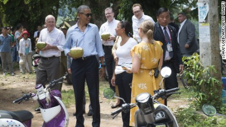 US President Barack Obama drinks from a coconut (2nd L) with US Ambassador to Laos Daniel Clune (L) as he makes a surprise stop for a drink alongside the Mekong River in Luang Prabang on September 7, 2016.
