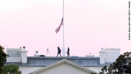 Security personnel take up positions beneath the national flag at half mast atop the White House 11 September 2001 in Washington, DC, following terrorist attacks that destroyed the World Trade Center in New York and damaged the Pentagon. AFP PHOTO/Robyn BECK (Photo credit should read ROBYN BECK/AFP/Getty Images)