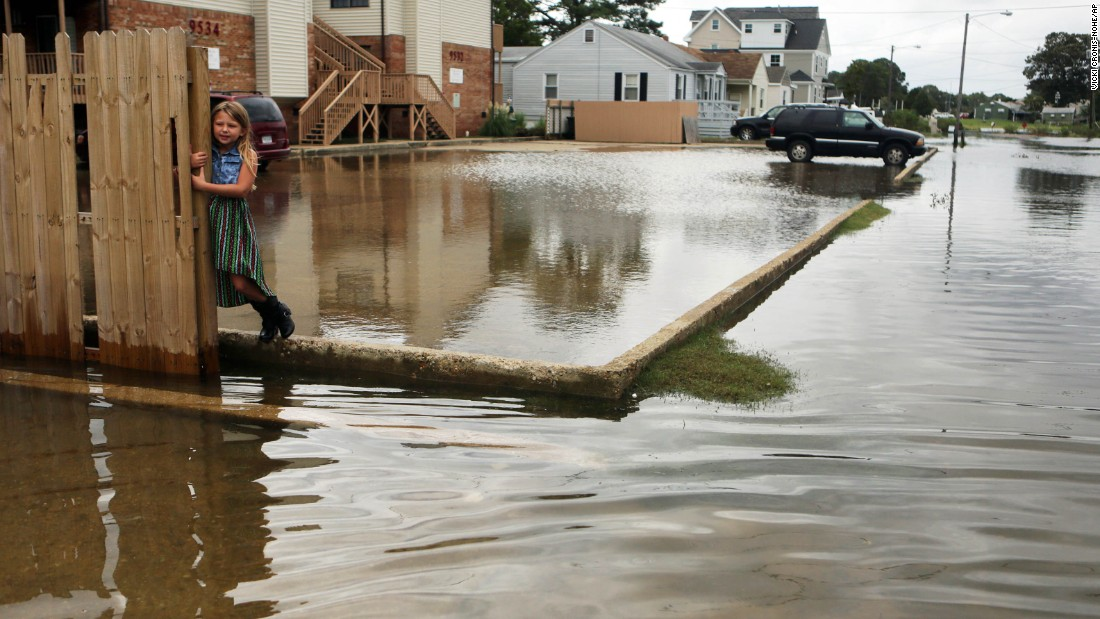 "Chloe Riffle, 7, looks on as she is surrounded by floodwater in Norfolk, Virginia, on Sunday, September 4. Labor Day plans for many residents living in coastal regions throughout the Northeast were affected<a href=""http://www.cnn.com/2016/09/03/us/tropical-storm-hermine/"" target=""_blank""> by heavy rain and winds from storm Hermine.</a>"