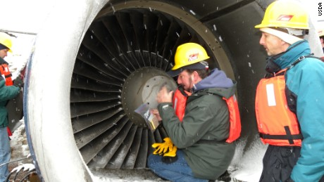 Mike Begier (left) of the USDA  investigates a damaged engine of US Airways Flight 1549 in 2009.