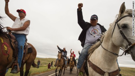Native Americans ride with raised fists to a sacred burial ground that was disturbed by bulldozers building the Dakota Access Pipeline (DAPL), near the encampment where hundreds of people have gathered to join the Standing Rock Sioux Tribe's protest of the oil pipeline slated to cross the nearby Missouri River, September 4, 2016 near Cannon Ball, North Dakota.  Protestors were attacked by dogs and sprayed with an eye and respiratory irritant yesterday when they arrived at the site to protest after learning of the bulldozing work. / AFP / ROBYN BECK        (Photo credit should read ROBYN BECK/AFP/Getty Images)
