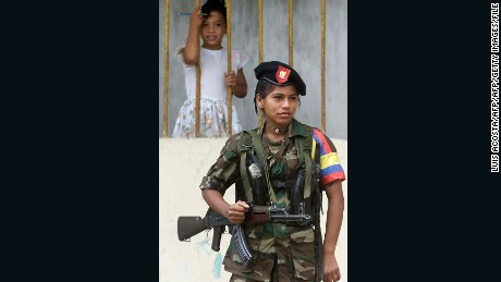A young girl watches as a  FARC fighter stands guard in Los Pozos during peace talks in 2001.