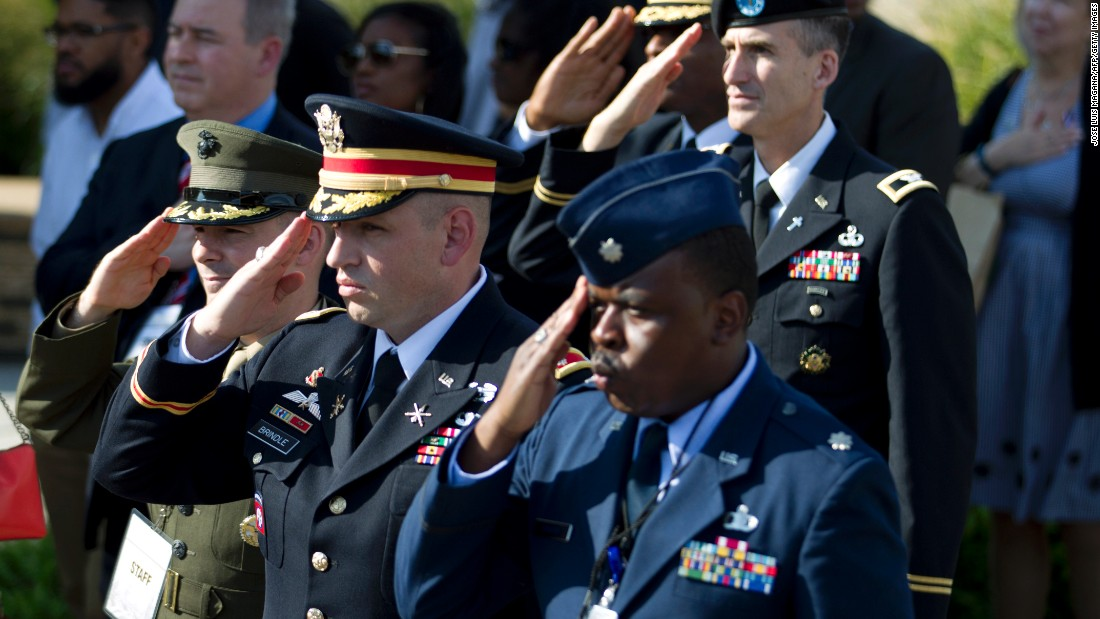 Military personnel salute during a ceremony Sunday to mark the 15th anniversary of the 9/11 attacks at the Pentagon Memorial in Washington, DC.