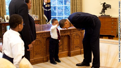 WASHINGTON - MAY 8:  In this handout from the The White House, U.S. President Barack Obama bends over so the son of a White House staff member can pat his head during a visit to the Oval Office May 8, 2009 in Washington, DC.  (Photo by Pete Souza/The White House via Getty Images)