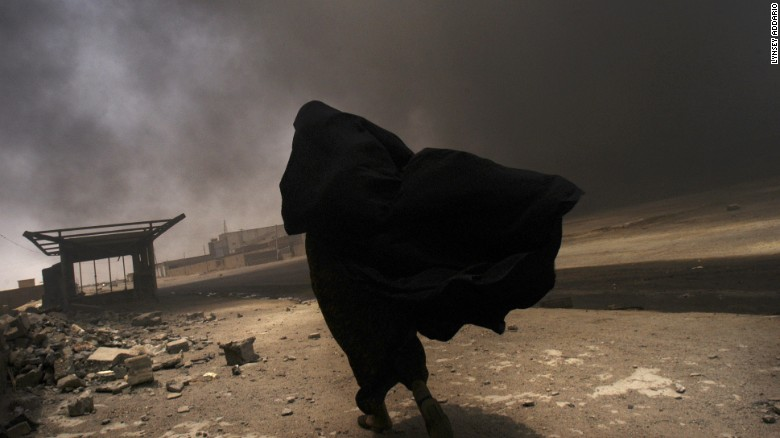 An Iraqi woman walks through a plume of smoke rising from a massive fire at a liquid gas factory as she searches for her husband in the vicinity of the fire in Basra, Iraq, May 26, 2003.  The fire was allegedly started by looters picking through the factory, and residents in the vicinity feared the explosion of the four liquid gas tanks on the premisis.   Weeks after the end of the war, looting continues to be one of the main problems for both Basra and Bagdad cities as coalition forces struggle to get life back to normal.