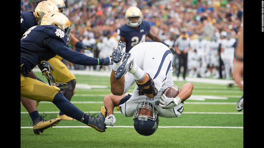 Nevada's Jarred Gipson flips as he is tackled by Notre Dame's Te'von Coney during a college game in South Bend, Indiana, on Saturday, September 10. Notre Dame won 39-10.