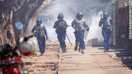 Zimbabwean anti-riot police chase opposition activists in August in Harare.