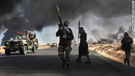 Libyan rebels battle government troops as smoke from a damaged oil facility darkens the skyline on March 11, 2011, in Ras Lanuf, Libya.