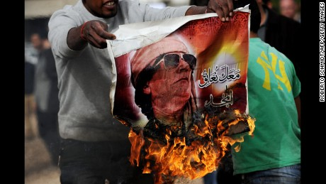 A man holds a burning poster of Moammar Gadhafi in Benghazi in March 2011.