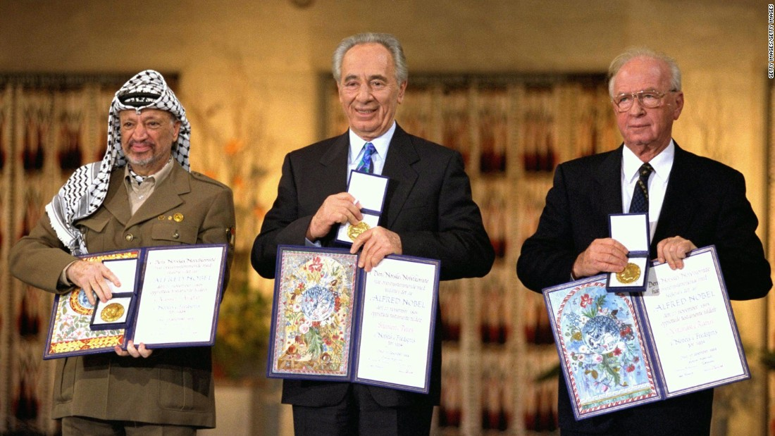 Palestinian leader Yasser Arafat, left, Israeli Foreign Minister Shimon Peres  and Israeli Premier Yitzhak Rabin display their Nobel Peace Prizes on December 10, 1994 in Oslo, Norway.
