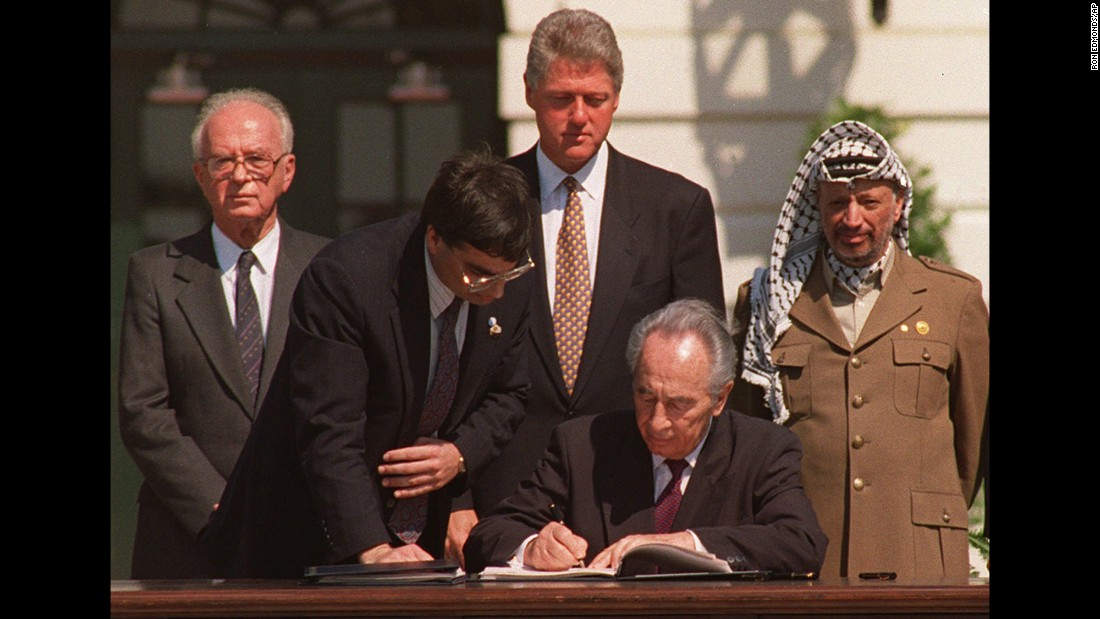 Israeli Foreign Minister Shimon Peres, with an unidentified aide, signs a peace agreement on September 13, 1993 between Israel and the Palestine Liberation Organization (PLO) in Oslo, Norway. Israeli Prime Minister Yitzhak Rabin, President Bill Clinton and PLO Chairman Yasser Arafat look on from behind.
