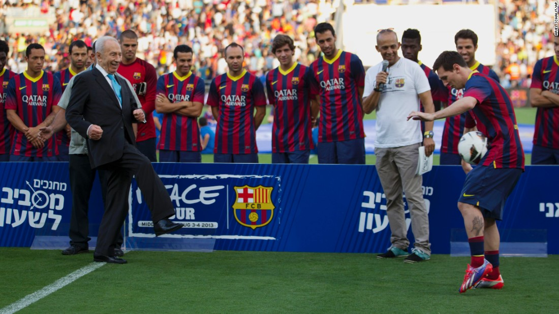 Israeli President Shimon Peres kicks the ball to FC Barcelona's striker Lionel Messi during a soccer clinic in Broomfield Stadium in Tel Aviv on August 4, 2013.