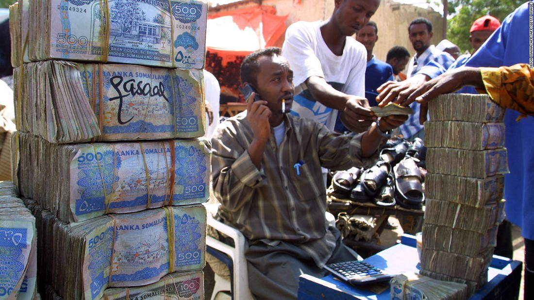 Somali money changer next to piles of banknotes on a busy street in Hargeisa.