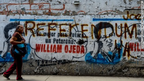 """TOPSHOT - A woman walks by a graffiti depicting late President Hugo Chavez and reading """"Referendum""""  in the Petare shantytown, Caracas on September 13, 2016.  Venezuelan authorities on Monday postponed announcing the dates for the final stage in the opposition-led push to call a referendum on removing embattled President Nicolas Maduro from power. / AFP / FEDERICO PARRA        (Photo credit should read FEDERICO PARRA/AFP/Getty Images)"""