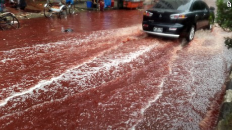 A car drives past a road turned red after blood from sacrificial animals on Eid al-Adha mixed with water from heavy rainfall in Dhaka, Bangladesh.