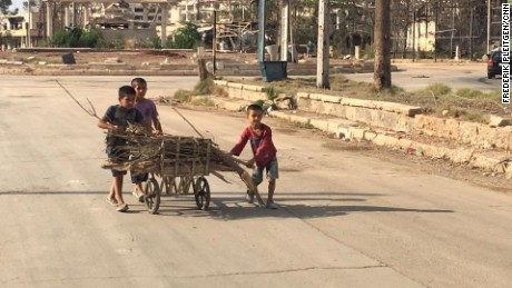 Children push a cart loaded with firewood collected in an Aleppo neighborhood.