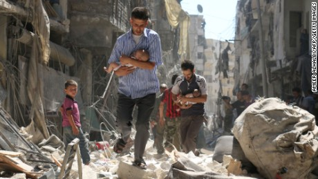 TOPSHOT - Syrian men carrying babies make their way through the rubble of destroyed buildings following a reported air strike on the rebel-held Salihin neighbourhood of the northern city of Aleppo, on September 11, 2016.