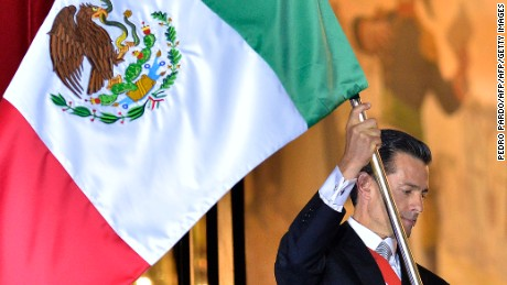 "Mexican President Enrique Pena Nieto waves the Mexican National Flag on the main balcony of the National Palace during ceremonies called ""The Shout"" marking the start of celebrations of Independence Day in Mexico City on September 15, 2016. / AFP / Pedro Pardo        (Photo credit should read PEDRO PARDO/AFP/Getty Images)"