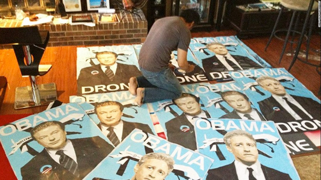 "Posters of actor Alec Baldwin and comedian Jon Stewart as ""Obama drones."""