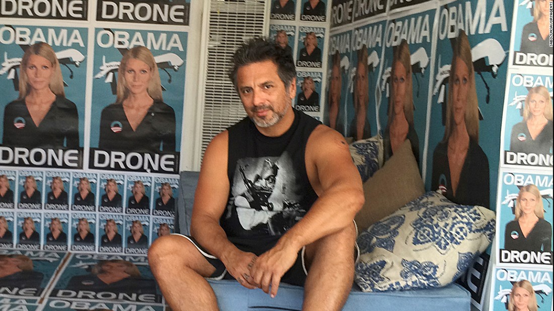 "The street artist Sabo rose to the national stage with art that often shocks, offends and confronts some of America's most controversial hot-button issues. Here, he poses in front of posters of actress Gwyneth Paltrow represented as an ""Obama drone."""