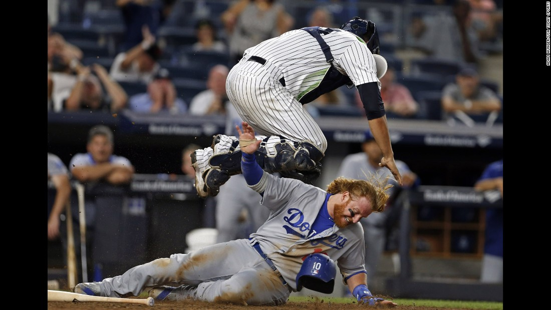 Justin Turner, a third baseman for the Los Angeles Dodgers, scores a run under New York Yankees catcher Gary Sanchez on Wednesday, September 14.