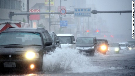 Vehicles drive through a flooded street as typhoon Malakas moves across Tokushima on September 20, 2016. A powerful typhoon ripped into southern Japan on September 20, dumping torrential rains on the region that left some communities partially submerged and forced dozens of flights to be cancelled. / AFP / JIJI PRESS / JIJI PRESS / Japan OUT        (Photo credit should read JIJI PRESS/AFP/Getty Images)
