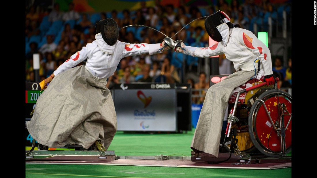 Chinese fencers Jing Bian, left, and Xufeng Zou compete for gold in the women's epee final.