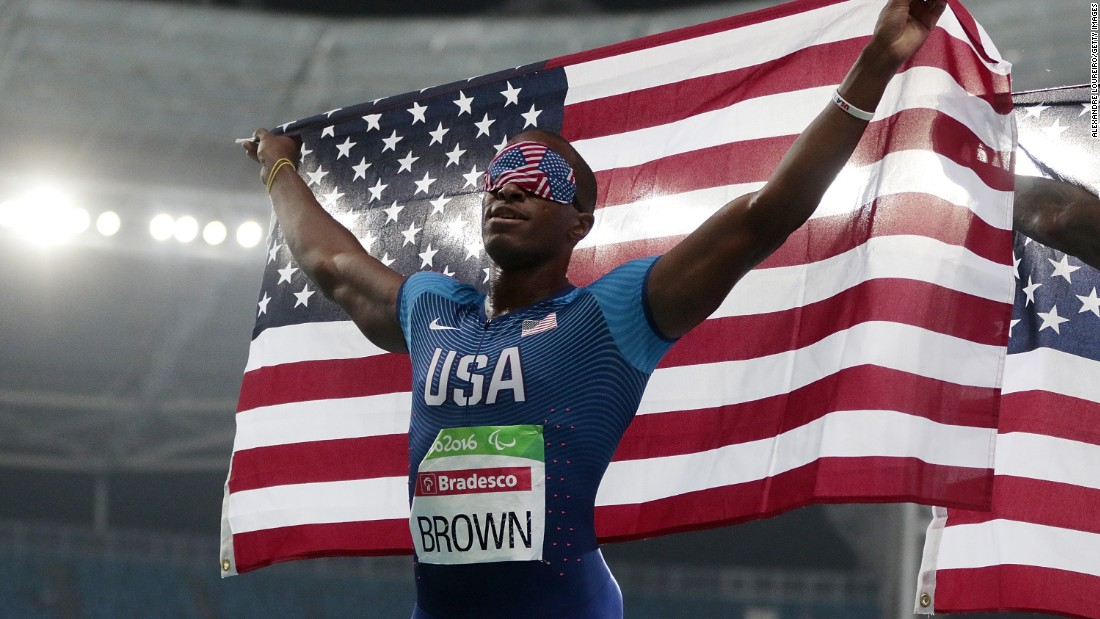 Paralympian David Brown waves the flag after winning gold in the 100 meters.