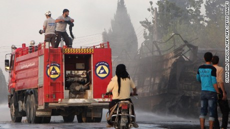 Members of the Syrian Civil Defence extinguish burning trucks carrying aid on the side of the road in the town of Orum al-Kubra on the western outskirts of the northern Syrian city of Aleppo on September 20, 2016, the morning after a convoy delivering aid was hit by a deadly air strike. The UN said at least 18 trucks in the 31-vehicle convoy were destroyed en route to deliver humanitarian assistance to the hard-to-reach town.  / AFP / Omar haj kadour        (Photo credit should read OMAR HAJ KADOUR/AFP/Getty Images)