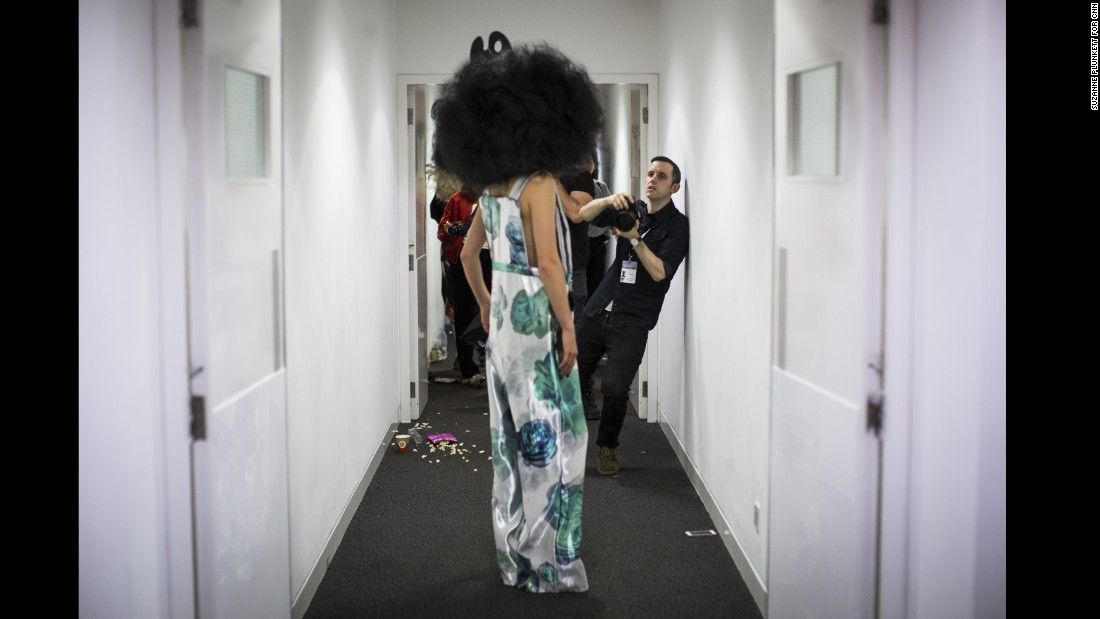 "A photographer shoots backstage before the Vin & Omi catwalk show. ""I shoot a lot of behind the scenes and backstage,"" says Price. ""The way I like to shoot is to quickly slip into position [in the pit] just towards the very end."""