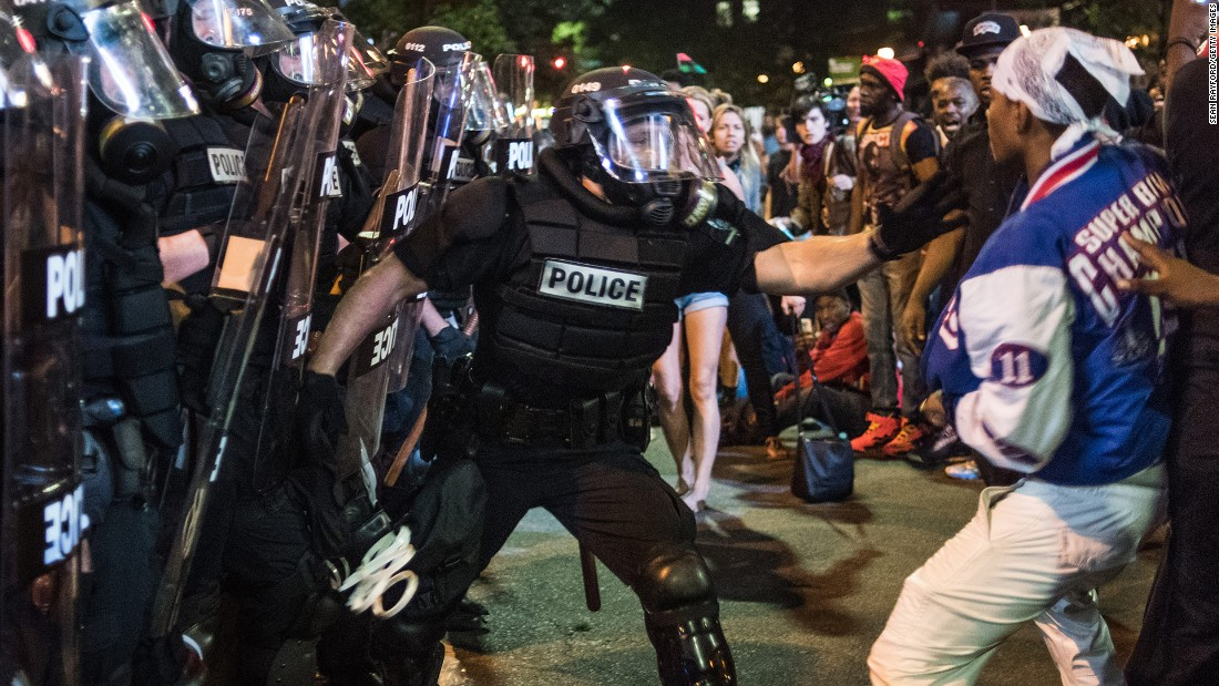 A police officer tries to grab a protester from the crowd.