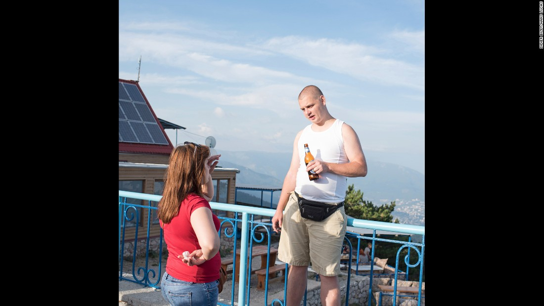 A man enjoys a beverage while visiting the Ai-Petri peak.
