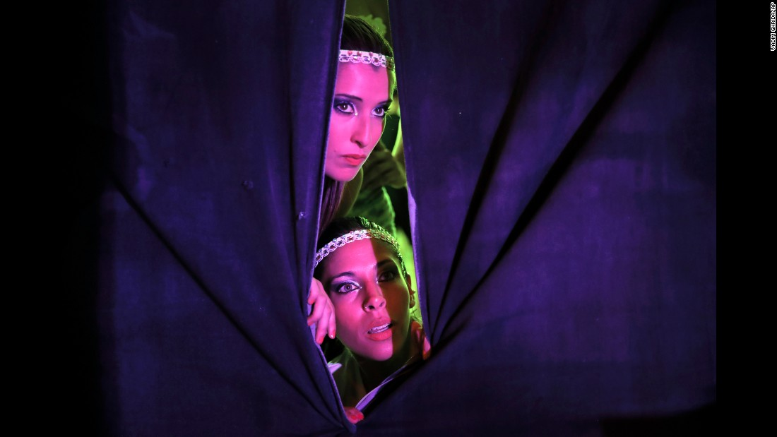 Ana Sofia Bigliardo, top, and Ana Laura Ruzicka watch from backstage during the doubles final of the World Pole Dance Championships. The fitness competition took place in Bucharest, Romania, on Friday, September 16.