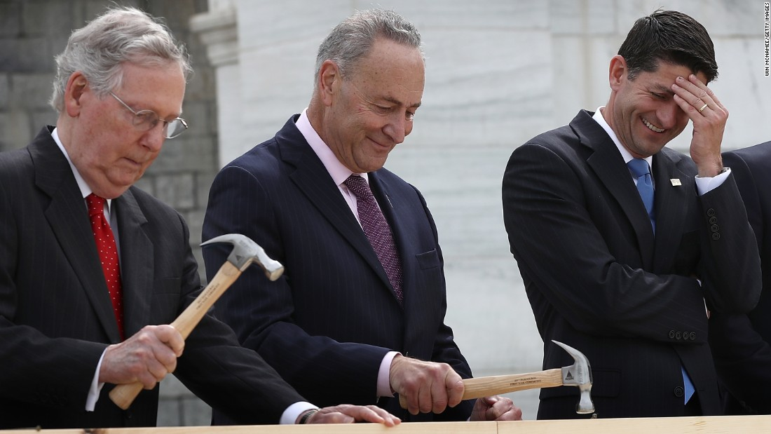 House Speaker Paul Ryan laughs as Senate Majority Leader Mitch McConnell, left, and US Sen. Chuck Schumer hammer ceremonial nails outside the US Capitol on Wednesday, September 21. Construction has begun on the platform where the next President will be inaugurated.