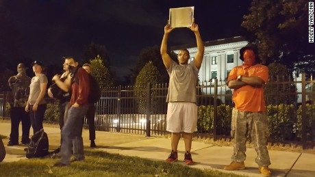 Alex Orange, 26, points a mirror at police Thursday.
