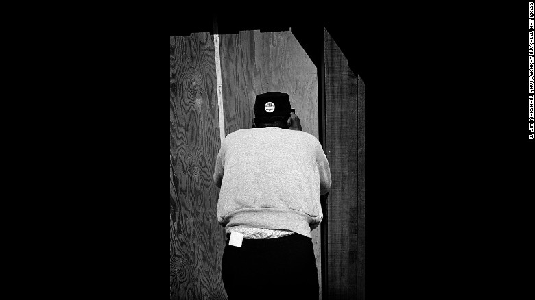 """A Dizzy Gillespie fan peeks through a hole backstage at Monterey in 1963. The button on the back of his head says """"Dizzy Gillespie for President."""""""
