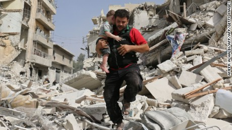 A Syrian baby is carried from the rubble following the bombing of a building in Aleppo on Wednesday, September 21.