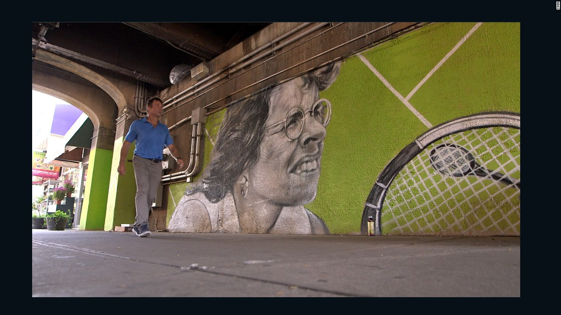 The competition was founded by Billie Jean King. Here Open Court host Pat Cash walks past a mural of the US tennis legend during CNN's visit to Forest Hills.