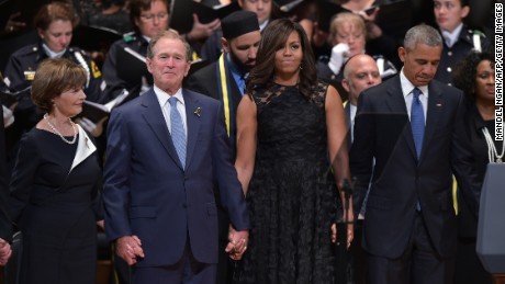 "The Bushes and the Obamas join hands during the singing of ""The Battle Hymn of the Republic"" during an interfaith memorial service for the victims of the Dallas police shooting on July 12, 2016, in Dallas."