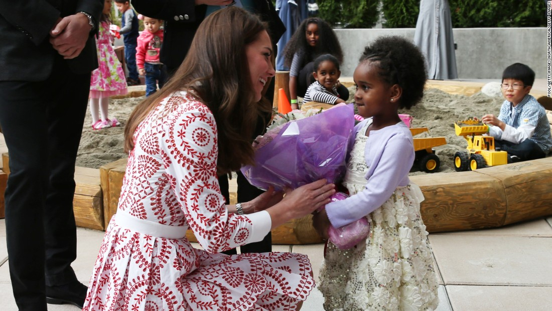 Catherine receives flowers from a young girl at the welcome center of the Immigrant Services Society of British Columbia.