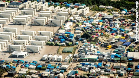 "This aerial view taken on August 16, 2016, in Calais, northern France shows the tents and the shipping containers housing migrants in the ""jungle"" camp where over 9000 migrants live according to different NGOs. Some groups believe 9,000 people are now crammed into the Jungle, which is a largely makeshift camp although 1,750 residents are housed in more permanent accommodation created from shipping containers. / AFP / PHILIPPE HUGUEN        (Photo credit should read PHILIPPE HUGUEN/AFP/Getty Images)"